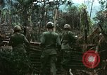 Image of U.S. soldiers dismantle and burn NVA huts in village Vietnam, 1968, second 10 stock footage video 65675021203