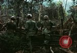 Image of U.S. soldiers dismantle and burn NVA huts in village Vietnam, 1968, second 11 stock footage video 65675021203