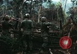 Image of U.S. soldiers dismantle and burn NVA huts in village Vietnam, 1968, second 13 stock footage video 65675021203