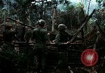 Image of U.S. soldiers dismantle and burn NVA huts in village Vietnam, 1968, second 14 stock footage video 65675021203
