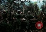 Image of U.S. soldiers dismantle and burn NVA huts in village Vietnam, 1968, second 15 stock footage video 65675021203