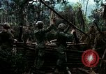 Image of U.S. soldiers dismantle and burn NVA huts in village Vietnam, 1968, second 16 stock footage video 65675021203