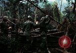 Image of U.S. soldiers dismantle and burn NVA huts in village Vietnam, 1968, second 17 stock footage video 65675021203