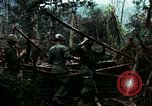 Image of U.S. soldiers dismantle and burn NVA huts in village Vietnam, 1968, second 18 stock footage video 65675021203