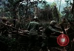 Image of U.S. soldiers dismantle and burn NVA huts in village Vietnam, 1968, second 19 stock footage video 65675021203