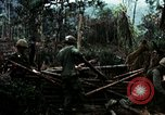 Image of U.S. soldiers dismantle and burn NVA huts in village Vietnam, 1968, second 20 stock footage video 65675021203