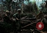 Image of U.S. soldiers dismantle and burn NVA huts in village Vietnam, 1968, second 21 stock footage video 65675021203