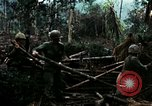 Image of U.S. soldiers dismantle and burn NVA huts in village Vietnam, 1968, second 22 stock footage video 65675021203