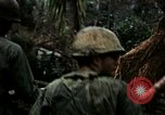 Image of U.S. soldiers dismantle and burn NVA huts in village Vietnam, 1968, second 23 stock footage video 65675021203