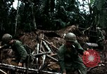 Image of U.S. soldiers dismantle and burn NVA huts in village Vietnam, 1968, second 43 stock footage video 65675021203
