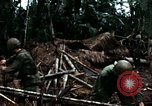 Image of U.S. soldiers dismantle and burn NVA huts in village Vietnam, 1968, second 44 stock footage video 65675021203