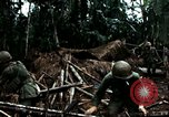 Image of U.S. soldiers dismantle and burn NVA huts in village Vietnam, 1968, second 45 stock footage video 65675021203