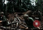 Image of U.S. soldiers dismantle and burn NVA huts in village Vietnam, 1968, second 46 stock footage video 65675021203