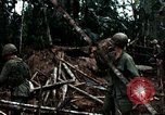 Image of U.S. soldiers dismantle and burn NVA huts in village Vietnam, 1968, second 48 stock footage video 65675021203