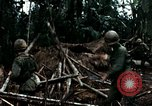 Image of U.S. soldiers dismantle and burn NVA huts in village Vietnam, 1968, second 49 stock footage video 65675021203