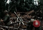 Image of U.S. soldiers dismantle and burn NVA huts in village Vietnam, 1968, second 51 stock footage video 65675021203