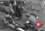 Image of Medics tend to wounded U.S. soldiers on beach Normandy France, 1944, second 2 stock footage video 65675022977