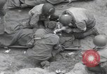 Image of Medics tend to wounded U.S. soldiers on beach Normandy France, 1944, second 15 stock footage video 65675022977