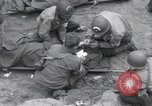 Image of Medics tend to wounded U.S. soldiers on beach Normandy France, 1944, second 18 stock footage video 65675022977