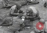 Image of Medics tend to wounded U.S. soldiers on beach Normandy France, 1944, second 19 stock footage video 65675022977