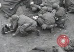 Image of Medics tend to wounded U.S. soldiers on beach Normandy France, 1944, second 24 stock footage video 65675022977