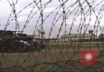 Image of view through barbed wire at airbase operations Vietnam, 1967, second 12 stock footage video 65675061936