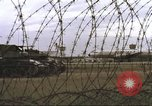 Image of view through barbed wire at airbase operations Vietnam, 1967, second 18 stock footage video 65675061936