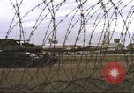 Image of view through barbed wire at airbase operations Vietnam, 1967, second 21 stock footage video 65675061936