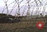 Image of view through barbed wire at airbase operations Vietnam, 1967, second 23 stock footage video 65675061936