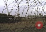 Image of view through barbed wire at airbase operations Vietnam, 1967, second 28 stock footage video 65675061936