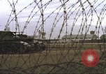 Image of view through barbed wire at airbase operations Vietnam, 1967, second 30 stock footage video 65675061936