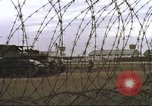 Image of view through barbed wire at airbase operations Vietnam, 1967, second 33 stock footage video 65675061936