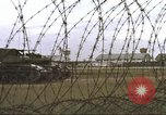 Image of view through barbed wire at airbase operations Vietnam, 1967, second 36 stock footage video 65675061936