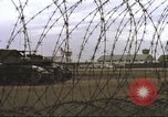 Image of view through barbed wire at airbase operations Vietnam, 1967, second 40 stock footage video 65675061936