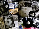 Some of The Ex-Bombers' recordings, merch, and press clippings.